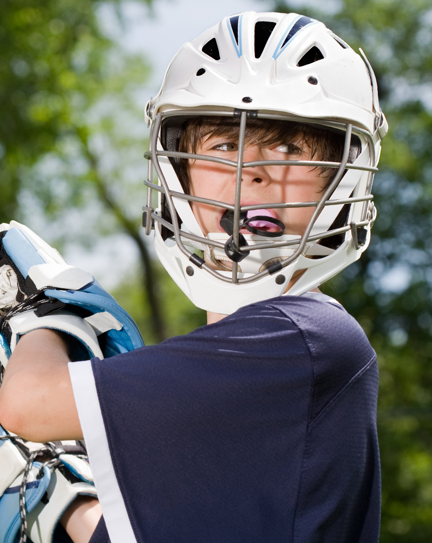 young boy playing lacrosse with a mouthguard in